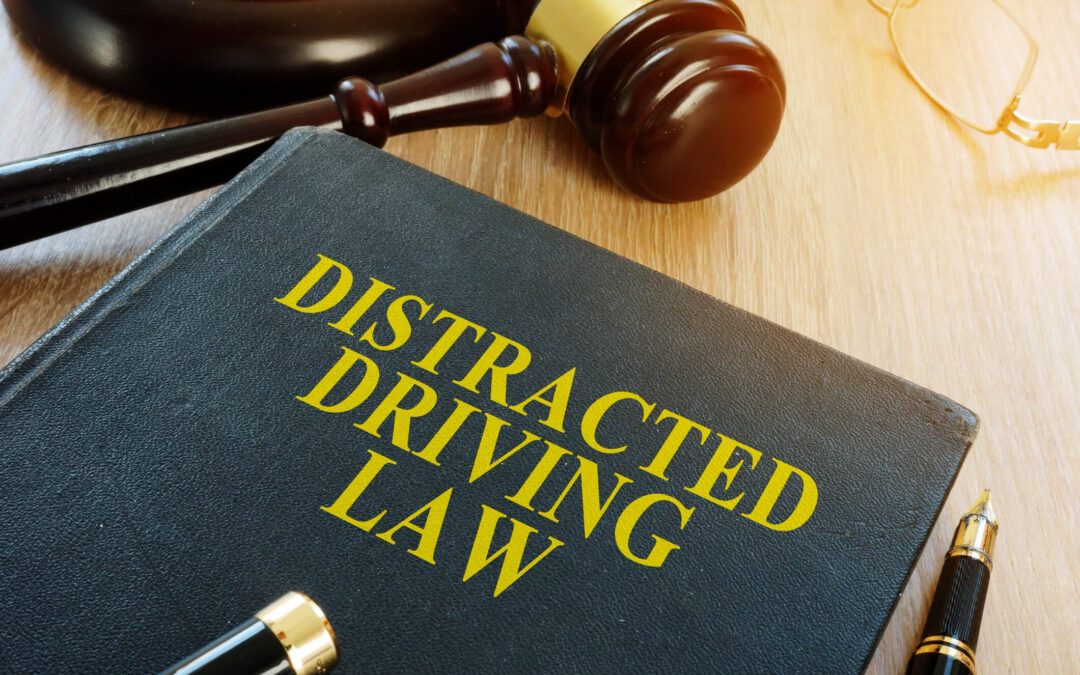 A black book with the words Distracted Driving Law printed on the front cover lays on top of a desk next to a gavel and block.